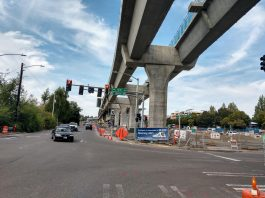 Elevated light rail with pylons next to a street in Northgate.