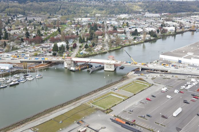 An aerial photo of the South Park Bridge under construction with the Duwamish Valley in the background.
